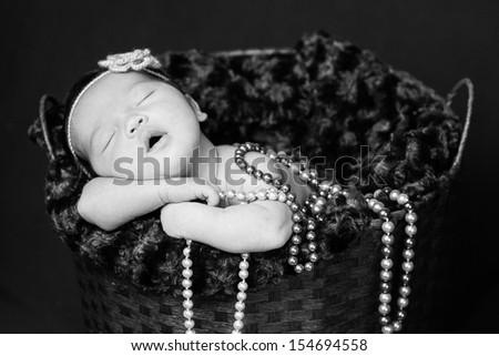 Newborn baby  sleeping inside a basket, resting on arms and elbows, on brown background. Wearing pearls and flower headband. Black and white. - stock photo