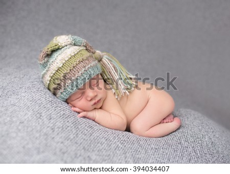 Newborn baby sleeping on blanket on his tummy, asleep in a knit hat, posed