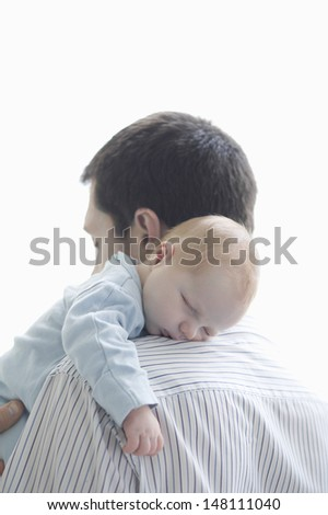 Newborn baby sleeping on father's shoulder over white background - stock photo