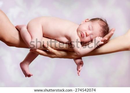 Newborn baby sleeping on parents hands, relax - stock photo