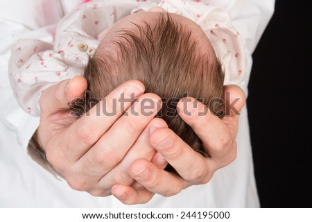 Newborn baby sleeping on the hands of his father - stock photo