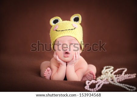 Newborn baby  sleeping, resting on her own hands and elbows, on brown background. Frog hat and frog pose. - stock photo
