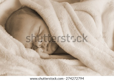 Newborn baby sleeping very quiet on a white blanket. - stock photo