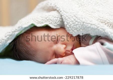 newborn baby sleeps under blanket - stock photo