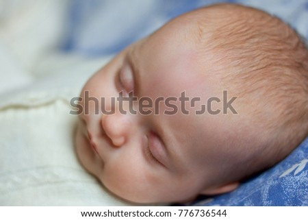 Newborn baby slepping wearing knitted overall