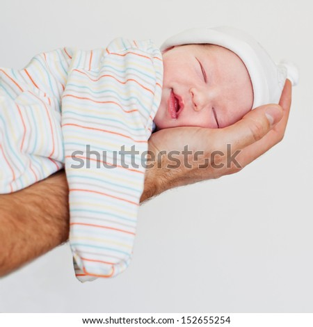 newborn baby smiling in his sleep on a hand on a white background - stock photo