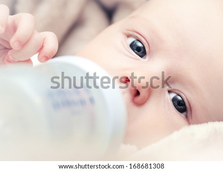 newborn baby sucking bottle - stock photo