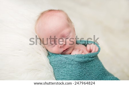 Newborn Baby swaddled, sleeping or napping, on soft white fur - stock photo