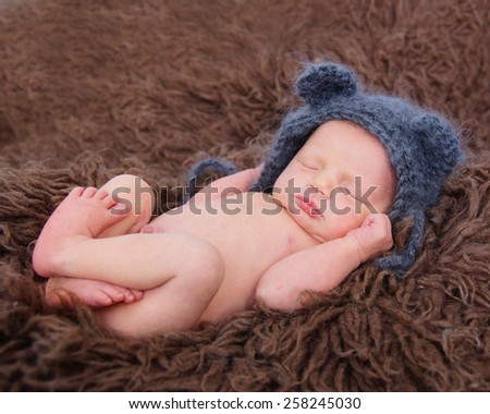 Newborn baby wearing cute teddy bear hat - stock photo