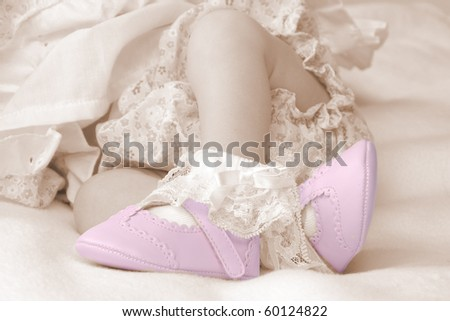 Newborn baby wearing little pink shoes - stock photo