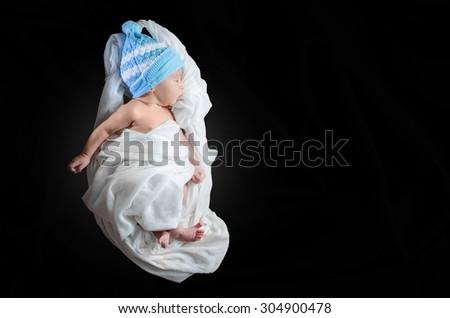 Newborn baby wearing white silk cocoon shape cloth & blue cap lying on black background - stock photo