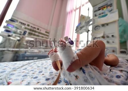 Newborn baby with cannula in the feet on a hospital bed - stock photo