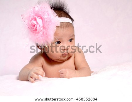 Newborn baby with headband on the head lying on blanket.  - stock photo