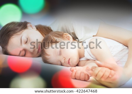 Newborn baby with mother sweet sleeping and holding hands on a white bed. Night, blur. Comfortable bed. Concept of baby care. Care concept. Healthy sleep. Healthcare - stock photo