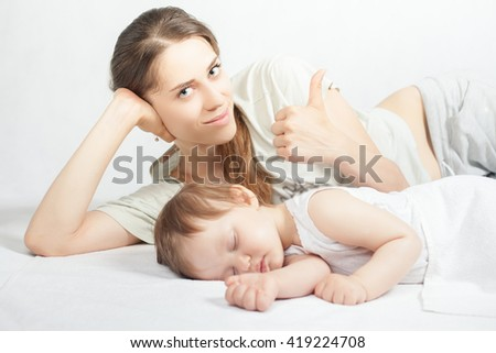 Newborn baby with mother sweet sleeping and holding hands on a white bed. Thumbs up gesture. Comfortable bed. Concept of baby care. Care concept. Healthy sleep. Healthcare - stock photo