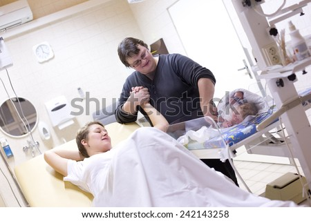 Newborn baby with parents after delivery - stock photo