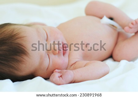 Newborn baby with umbilical cord sleeping on his first day in life