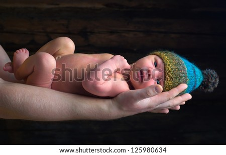 Newborn baby with winter hat in fathers hands - stock photo