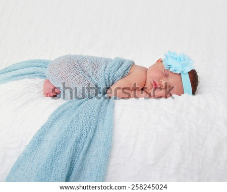 Newborn baby wrapped in turquoise fabric with flower headband - stock photo