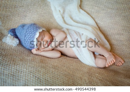 Newborn boy in hat is sleeping in the bed