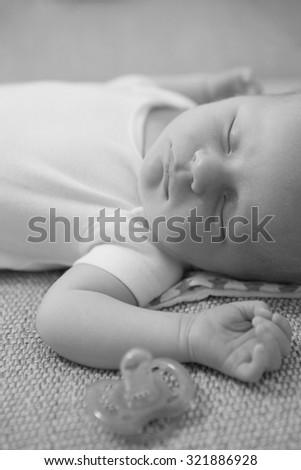 Newborn boy sleeping on the couch. High iso. Shallow DOF - stock photo
