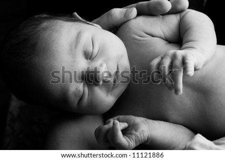 Newborn child in the hands of mother