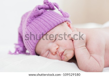 newborn child with a ridiculous violet hat sleeps, lying on a stomach - stock photo