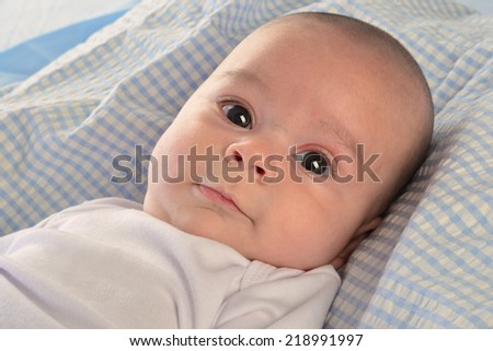 newborn close up lying on a soft bed.