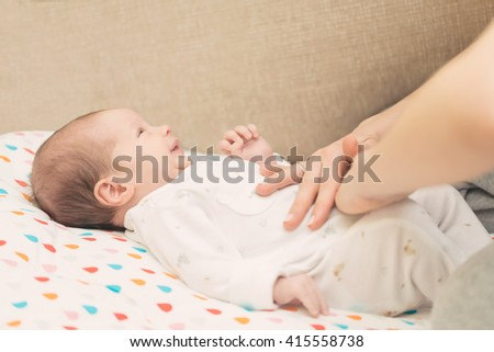 Newborn colicky baby dressed in white laying on her back, mother's hand on her tummy helping her with colic - stock photo