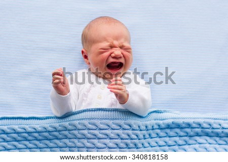 Newborn crying baby boy. New born child tired and hungry in bed under blue knitted blanket. Children cry. Bedding for kids. Infant screaming. Healthy little kid shortly after birth. Cable knit textile - stock photo