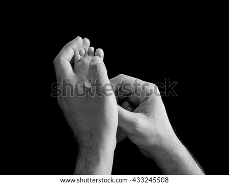 Newborn feet inside a his dad or mom hand isolated on black background - stock photo