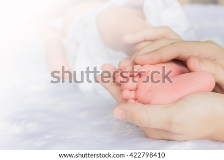Newborn feet on soft hand mom.