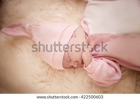 newborn girl in a pink dress sleeping on sheep skin on a light background