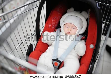 Newborn girl in car seat in a shopping cart - stock photo