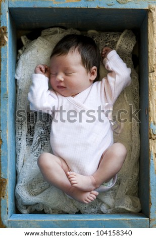 newborn girl lying in a box - stock photo