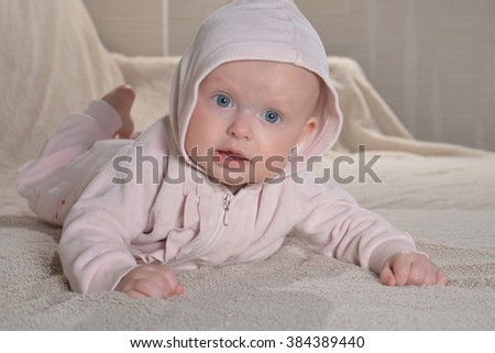 newborn girl wearing pink bathrobe and lying in her bed looking  - stock photo
