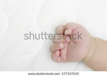 newborn hand on white bed