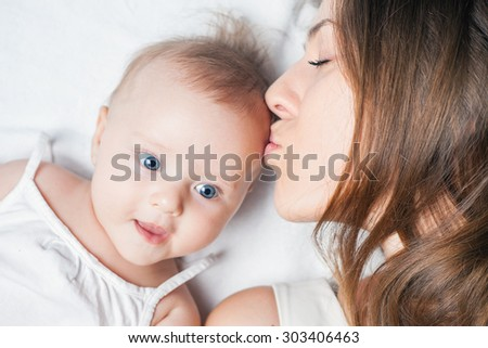 Newborn happy baby girl lying near her mother on a white bed. Mum kissing her daughter. Mothercare is most important in baby life