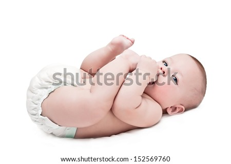 newborn in a diaper pulls a foot in a mouth - stock photo