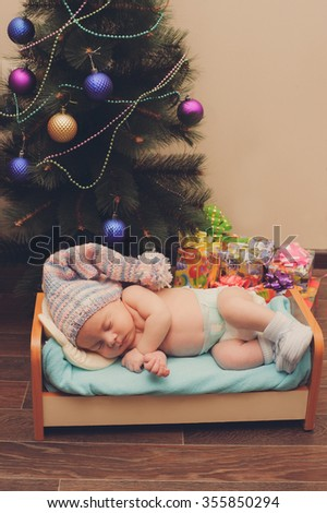 Newborn in a hat gnome sleeps at home besides Christmas tree, waiting for Santa Claus, around a lot of presents. Holiday home decoration. Newborn baby sleeps in a crib doll.  - stock photo