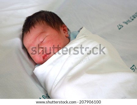 newborn infant asleep in the blanket in delivery room - stock photo