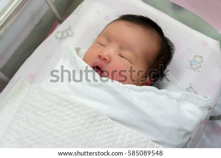 Newborn infant asleep in the blanket in delivery room, first days after birth