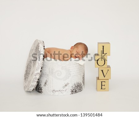 Newborn infant baby in hat box with LOVE spelled in bricks - stock photo