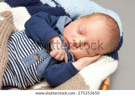 Newborn infant baby sleeping in a basket - stock photo
