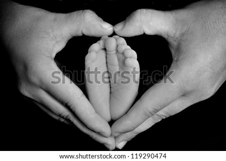 Newborn infant feet in mother's heart-shaped hands