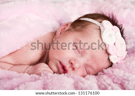 Newborn infant girl sleeping on a pink blanket - stock photo