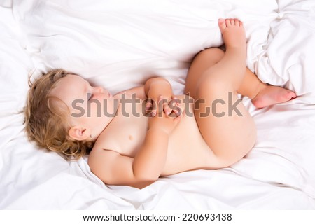 Newborn Infant sleeping on the bed - stock photo