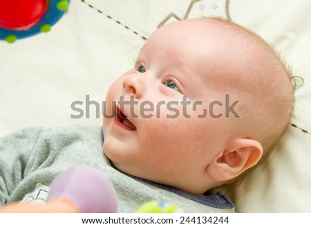 Newborn laying in a bed on a blanket watching up to the bright plastic toy - stock photo
