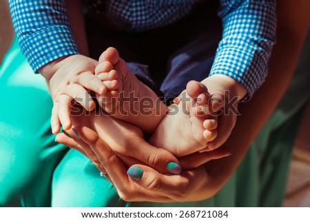 Newborn legs in mothers hands - stock photo