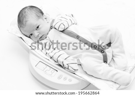 newborn on the scales looking at the camera on a white background ( black and white ) - stock photo